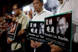 Pro-democracy activists mourn the death of Chinese Nobel Peace laureate Liu Xiaobo, outside China's Liaison Office in Hong Kong. PHOTO: REUTERS