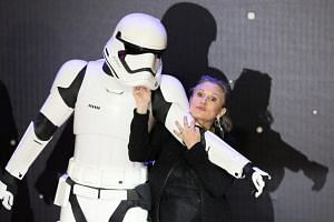 Carrie Fisher poses for cameras as she arrives at the European Premiere of Star Wars, The Force Awakens in Leicester Square, London, on December 16, 2015.