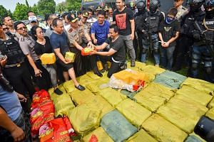 Indonesian police displaying one of the suspects (right, wearing mask with hands tied) and drugs seized during the raid in Anyer, Banten, on Thursday. The drugs were valued at almost 2 trillion rupiah (S$206 million).