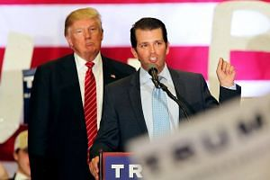 Mr Donald Trump (left) listens to his his son Donald Trump Jr speaking to supporters during a rally at Lakefront Airport, on March 4, 2016.