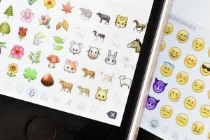 A picture shows emoji characters also known as emoticons on the screens of two mobile phones in Paris on Aug 6, 2015.