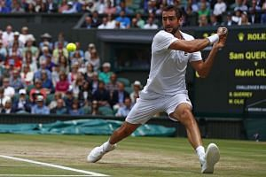 Croatia's Marin Cilic returns against US player Sam Querrey during their men's singles semi-final match on the eleventh day of the 2017 Wimbledon Championships at The All England Lawn Tennis Club in Wimbledon, southwest London, on July 14, 2017.