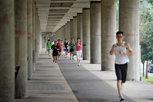 Joggers along the stretch of the covered fitness area under the MRT tracks along Ang Mo Kio Avenue 8.