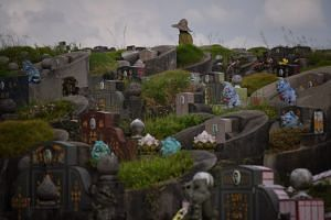 A caretaker seen amongst graves at Block 11 at the Chinese Cemetery.
