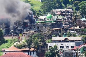 This photo taken on June 26, 2017 shows smoke billowing from a burning house after an aerial bombing on Muslim militant positions in Marawi, on the southern island of Mindanao.