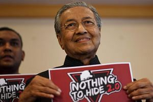 Malaysia's former prime minister Mahathir Mohamad holds a placard for the second