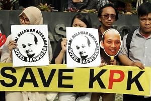 """Protesters outside the KPK building in Jakarta carrying placards which read: """"We fight together with Novel Baswedan"""". Mr Novel, a veteran graft investigator, suffered serious facial injuries after he was attacked with acid on April 11. His assailants"""