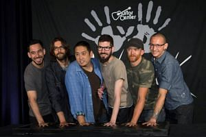 Members of rock band Linkin Park (left to right) Mike Shinoda, Rob Bourdon, Joe Hahn, Brad Delson, Dave Farrell and Chester Bennington put their handprints in cement as they are inducted into Guitar Center's RockWalk in Los Angeles, California.