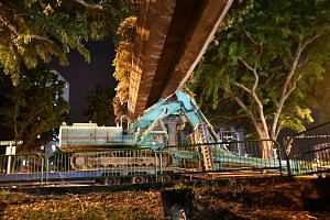"""9.30pm (July 21): The arm of an excavator being ferried on a trailer crashed into an overhead pedestrian bridge along Balestier Road. """"There was a very loud noise. The bridge moved and then stood still,"""" said one witness."""