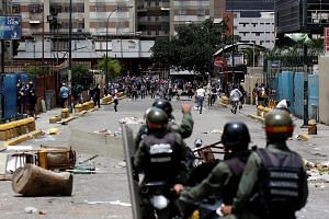 Demonstrators clashing with riot security forces while participating in a strike on Thursday in Caracas, Venezuela.