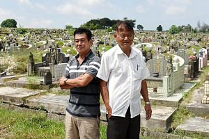 Gravedigger Yow Moom Lam (left) with Mr Johnny Tan of Chua Chu Kang Marble Company. Mr Tan said Mr Yow explains to family members present at an exhumation what each retrieved bone is.