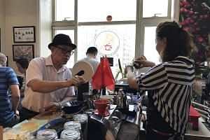 Mr Thomas Tian, 63, in his Beijing workshop with student Michelle Cai. Mr Tian teaches people how to roast coffee beans and how to make a good cup of coffee.