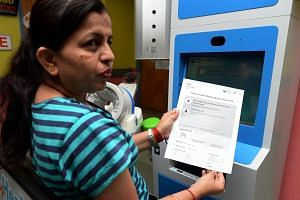 A patient collecting her result slip from the MyHealth Kiosk, which measures height, weight and a person's body mass index before spitting out a printed report.