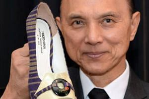 Designer Jimmy Choo poses with his one-off shoes made with materials from Japan's Fukushima area in an April 2014 photograph.