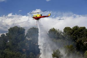 A firefighting helicopter drops water over a forest fire in Carros near Nice, southern France, on July 25, 2017.