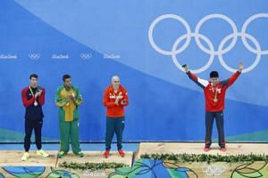 (right to left) Joint silver medalists, Michael Phelps, Chad Guy Bertrand le Clos, Laszlo Cseh and gold medalist Joseph Schooling celebrate on the podium during the Men's 100m Butterfly Final medals ceremony on Aug 12, 2016 in Rio de Janeiro, Brazil.