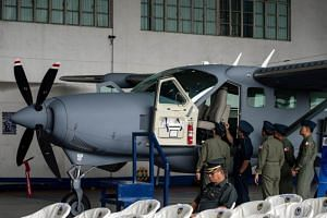 cap: Philippine Air Force pilots checking a Cessna-208B surveillance aircraft acquired from the US government, in Manila on July 27, 2017.