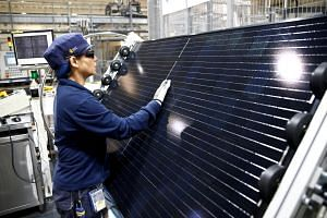 An employee makes a final inspection on panels during a tour of an REC solar panel manufacturing plant in Singapore.