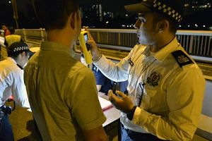 A driver going through a breathalyzer check by a traffic police officer at a road block along Nicoll Highway on July 24, 2014.
