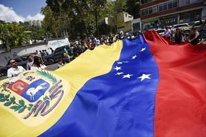 Voters hold a large Venezuelan flag outside of a polling station during a symbolic plebiscite in Caracas on July 16, 2017.
