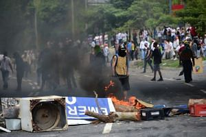 Anti-government activists set up barricades during a protest against the elections in Caracas on July 30, 2017.