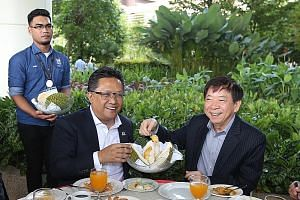 Malaysia's Minister in the Prime Minister's Department Abdul Rahman Dahlan with Coordinating Minister for Infrastructure Khaw Boon Wan, who is also Transport Minister, enjoying durian during a tea break at Afiniti Medini, after a site visit to the mi