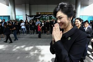 Ousted former Thai prime minister Yingluck Shinawatra gestures in a traditional greeting as she leaves the Supreme Court in Bangkok.