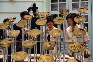 Hong Kong Chief Executive Carrie Lam and Senior Minister of State for Culture, Community and Youth Sim Ann look at exhibits at the Asian Civilisations Museum on Aug 2, 2017.