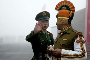 A Chinese soldier next to an Indian soldier at the Nathu La border crossing between India and China in India's northeastern Sikkim state.