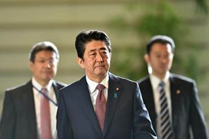 Japan's Prime Minister Shinzo Abe (centre) arrives at his official residence to attend a cabinet meeting in Tokyo on Aug 3, 2017.