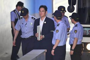 Lee Jae-Yong (centre), the vice-chairman of Samsung Electronics, is escorted by prison guards as he arrives at the Seoul Central District Court in Seoul on August 2, 2017.
