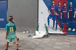 A new poster being put up outside Barcelona's Camp Nou stadium. The previous poster featured Barca forward Neymar, who is expected to land in Paris today ahead of his impending move to PSG despite a hitch. Spain's LaLiga turned down the Brazilian's l