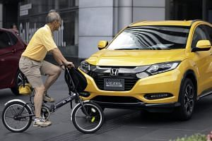 A passing cyclist looks at a Honda Vezel Hybrid vehicle on display outside a company showroom in Tokyo.