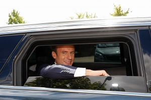 Macron leaves after a visit to a recreational centre for children in Moisson, on Aug 3, 2017.