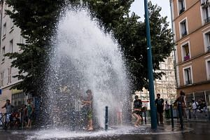 Children cooling off in water from a fire hydrant in France in June. Scientific findings suggest heatwaves could cause 99 per cent of all future weather-related deaths in Europe.