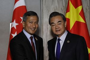 China's Foreign Minister Wang Yi (right) and his counterpart from Singapore Vivian Balakrishnan (left) pose before their bilateral talks at the Association of South East Asian Nations Foreign Ministers' Meeting and Related Meetings in Manila, Phili