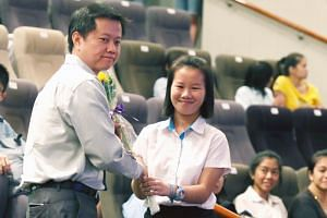 Mr Tan Guan Seng with his student Gerlynn Ng at the CDAC tuition programme awards ceremony yesterday. Miss Ng passed mathematics for the first time with Mr Tan's help.