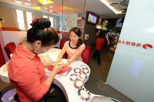 Haidilao in Singapore offers manicures to waiting customers.
