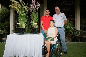 Joseph Schooling and Yip Pin Xiu with Dr Nigel Taylor, group director of the Singapore Botanic Gardens, alongside the orchid varieties that have been named after the two swimmers.