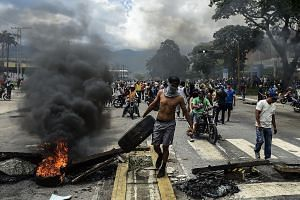 Anti-government activists building a barricade in Venezuela's third city, Valencia, on Sunday, a day after the new Constituent Assembly - loyal to President Nicolas Maduro - started functioning in the country. The controversial assembly has quickly u