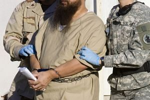 A detainee is escorted by military guards at the US Naval base at Guantanamo Bay, Cuba, in a file photo.