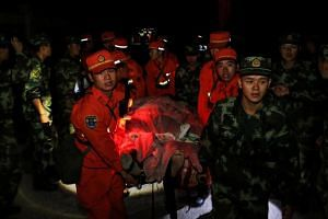Chinese paramilitary police carry a survivor after an earthquake in Jiuzhaigou county, Ngawa prefecture, Sichuan province, on Aug 9, 2017.