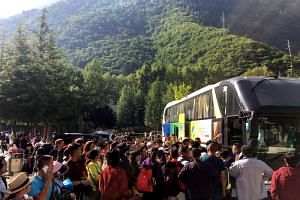 Tourists wait to be evacuated after an earthquake in Jiuzhaigou in China's southwestern Sichuan province on August 9, 2017. China on August 9 evacuated tens of thousands people in its mountainous southwest after a strong earthquake killed at least 19