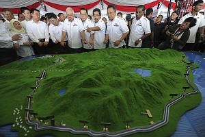 Malaysian Prime Minister Najib Razak and China's State Councillor Wang Yong (front row, third from left) viewing a model of the East Coast Rail Link in Kuantan yesterday. Mr Najib described the rail link as a