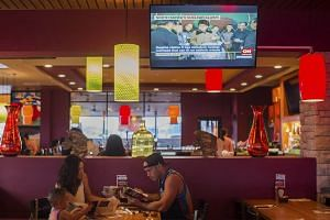 A family dines as news about North Korea plays on a TV at an Applebee's in Tamuning, Guam, on Aug 9, 2017.