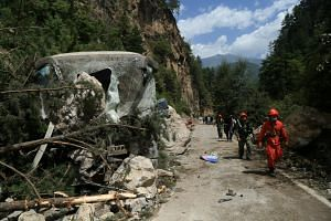 Rescue workers walk past a collapsed area after an earthquake in Jiuzhaigou county.