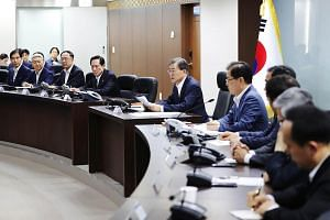 South Korean President Moon Jae In (centre) presides over an emergency meeting with National Security Council members at the presidential Blue House in Seoul,  on July 29, 2017.