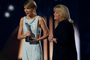 Taylor Swift accepts the Milestone Award from her mother Andrea at the 50th Annual Academy of Country Music Awards.