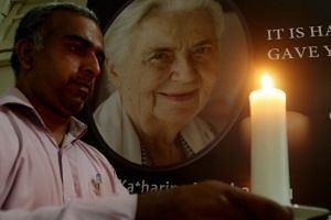 A man holds a candle in front of a portrait of German nun Ruth Pfau, following her death in Karachi.