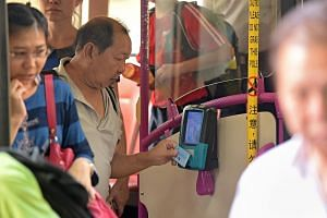 An elderly man tapping his ezLink card as he alights a bus at a bus stop at Braddell MRT Station.